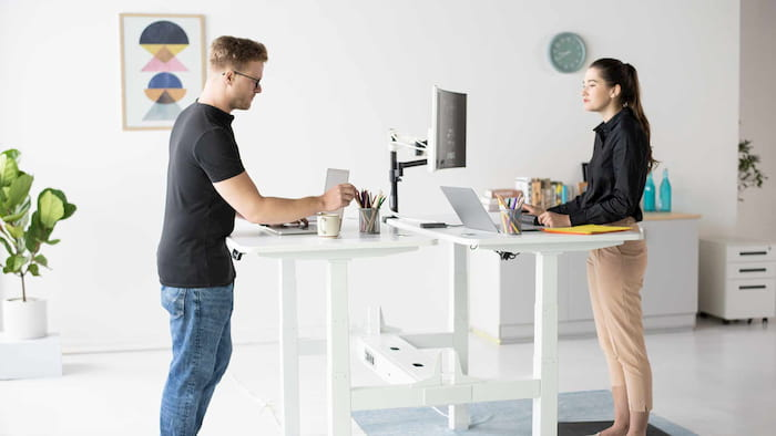 a girl and a man working on a modern white standing desks