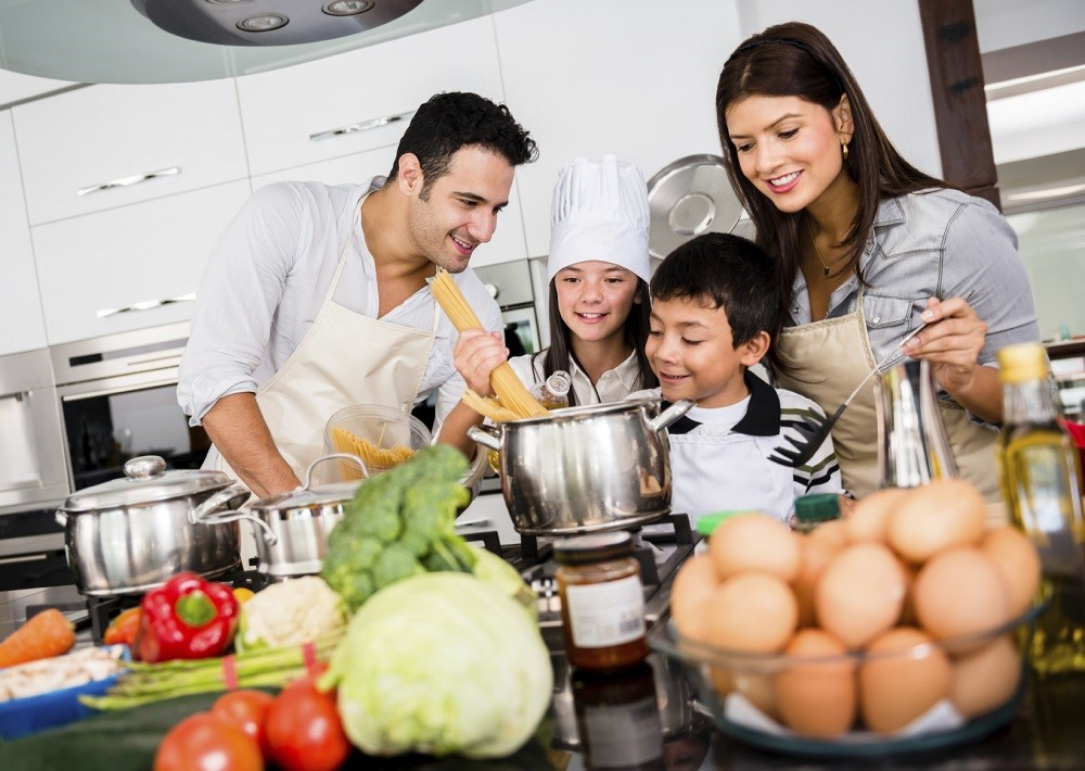 picture of mother, father and one little girl and little boy as a family cooking pasta and a lot of vegetable and eggs in the kitchen