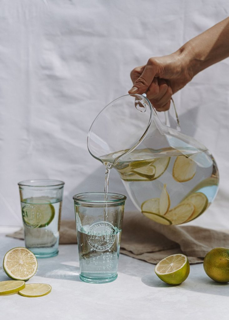 picture of a water pouring in glass with  lemons