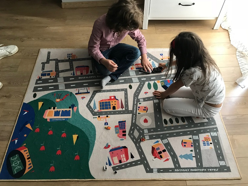 boy and girl playing on a educational rug